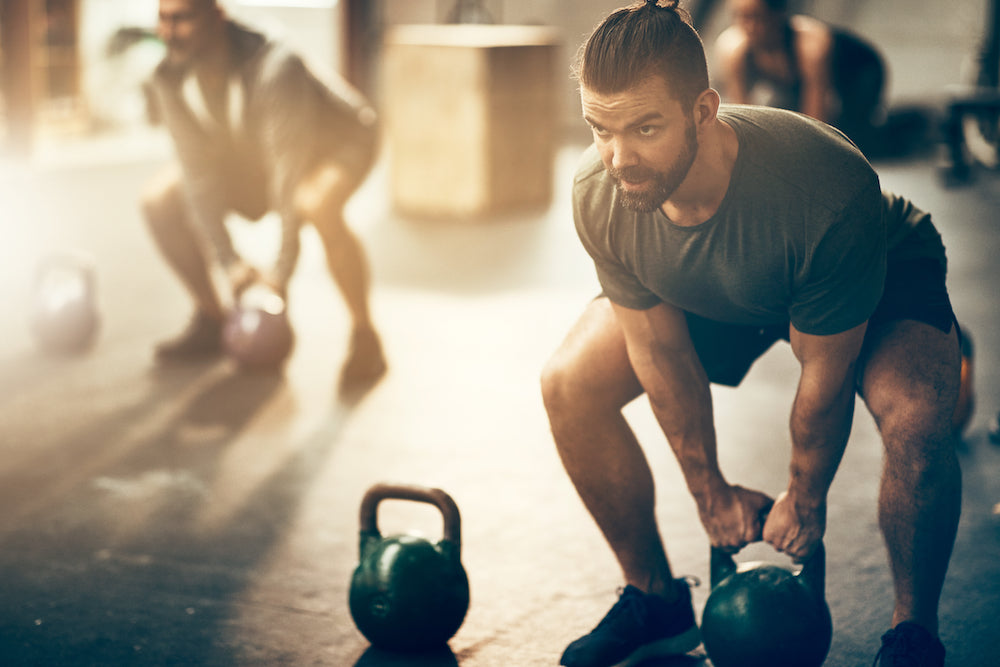 Fit man in squat position lifting kettle bell in a gym