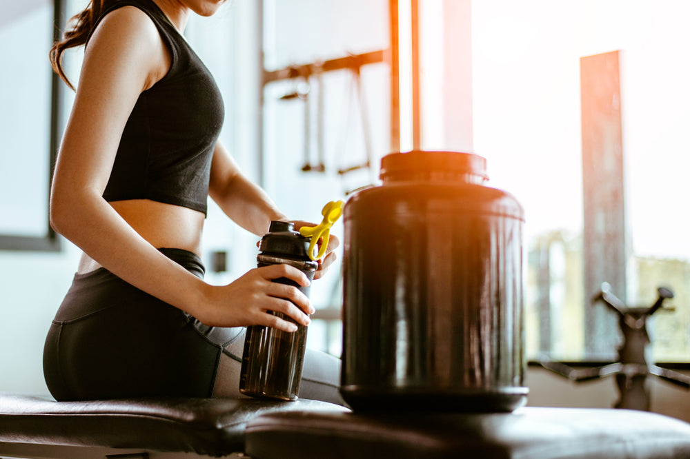 Woman making protein drink in the gym