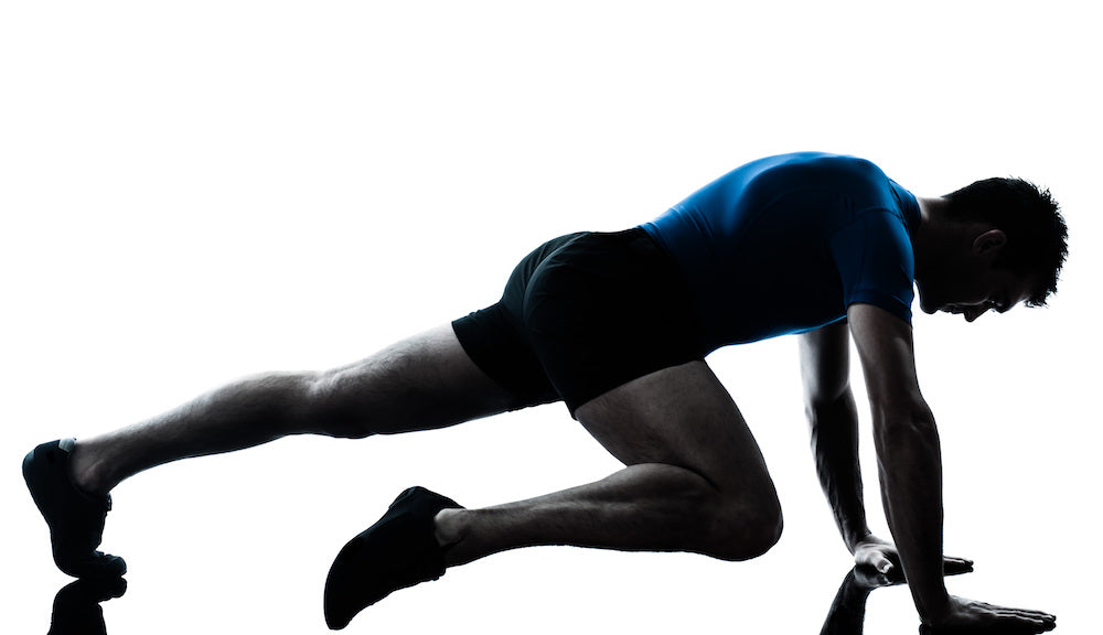 Silhouette of a fit man doing a step plank