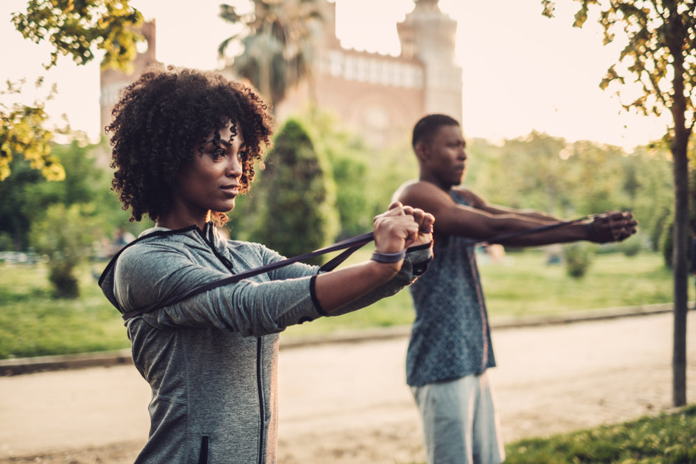 Couple in the park working out with resistance bands