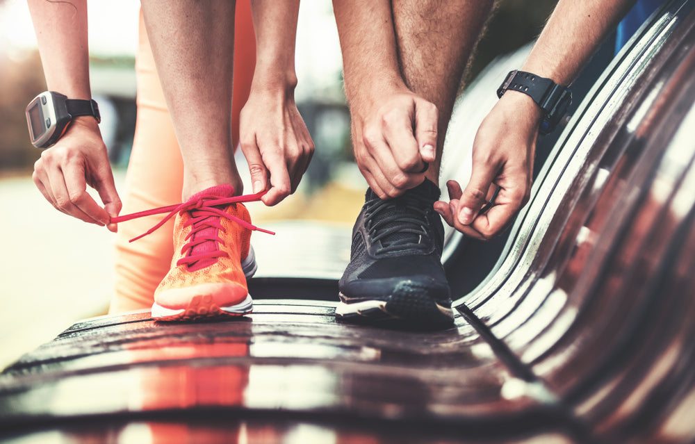 Two people tying their shoes on a bench, getting ready to workout