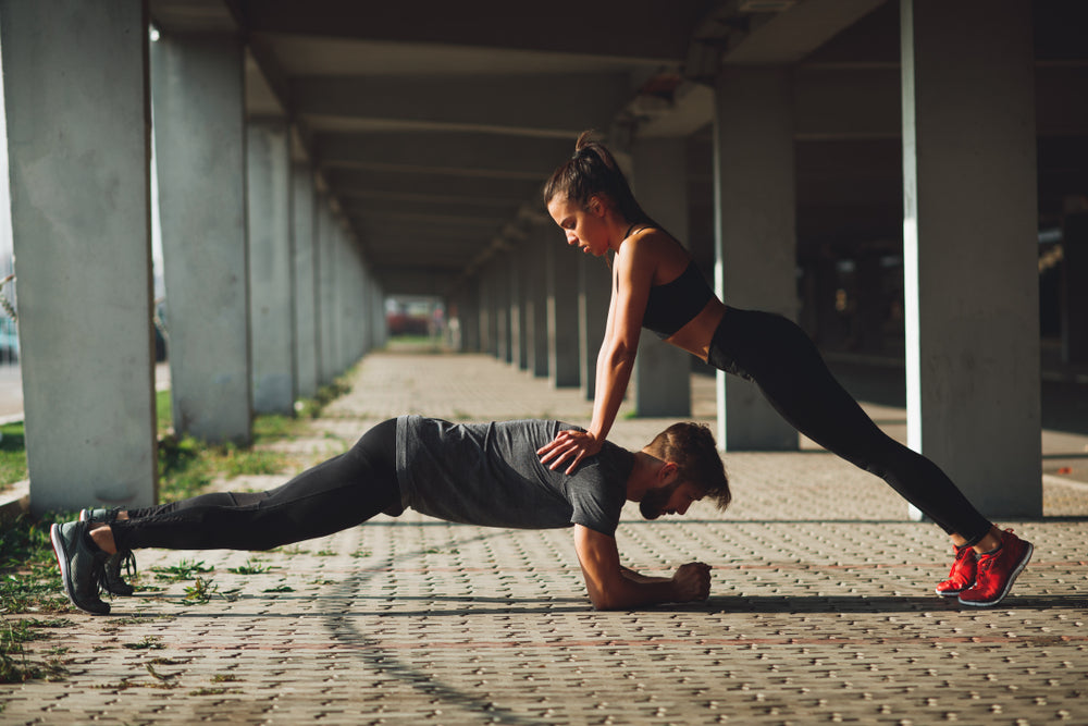 Two people preforming plank incline push up exercise