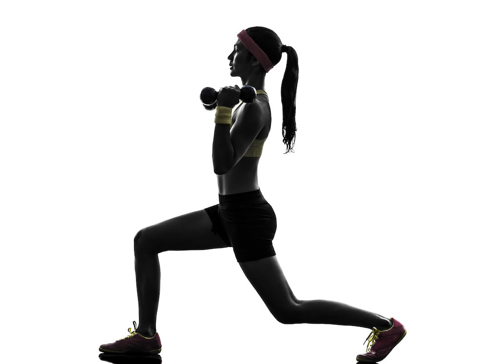 Silhouette of a fit woman doing an overhead dumbbell lunge
