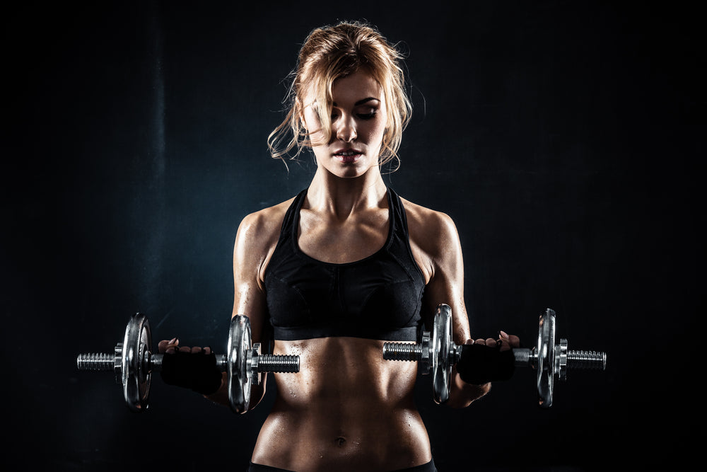 Fit woman lifting barbells