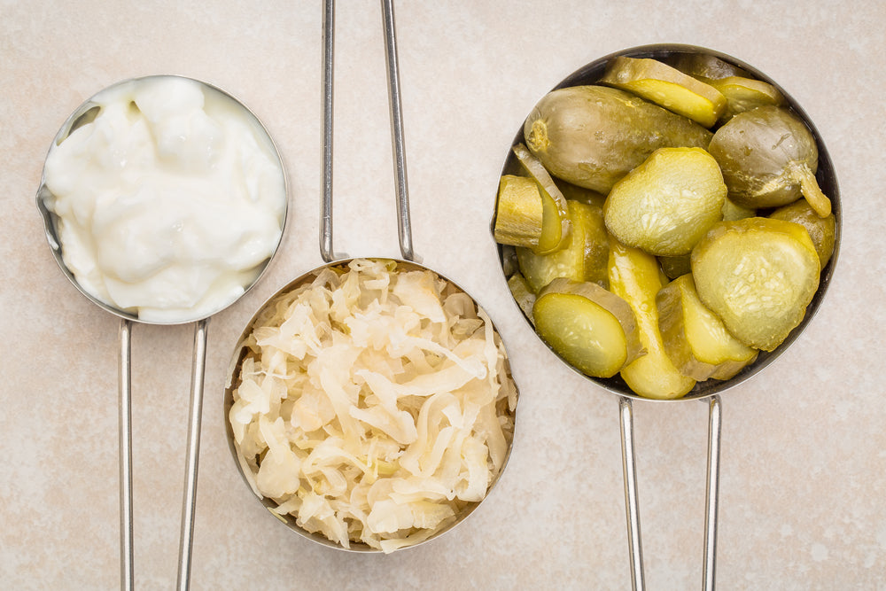 Image of probiotic foods - yogurt, pickle and sauerkraut in measuring cups