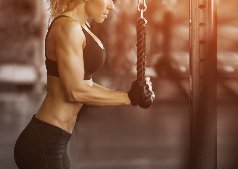 Fit woman doing tricep rope pulldown in gym
