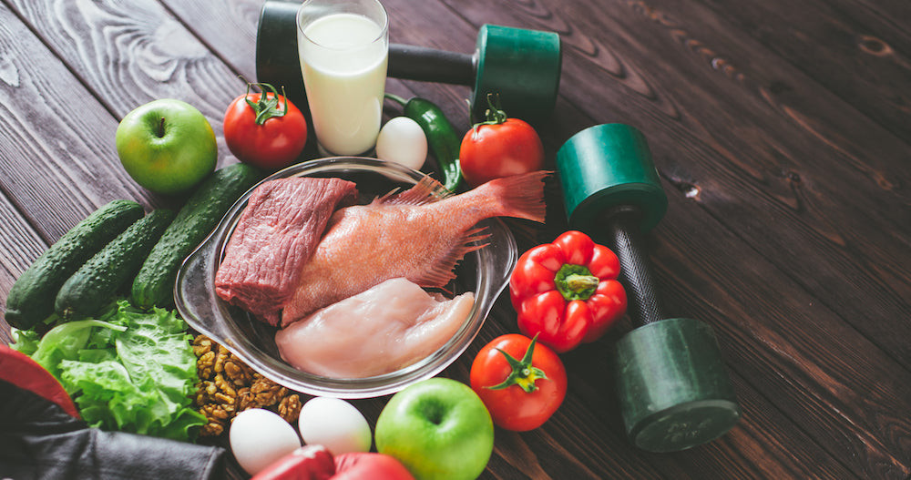 Protein and veggie surrounded by weights showing anabolic diet