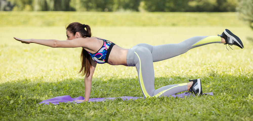 Woman performing bird dog plank in a park