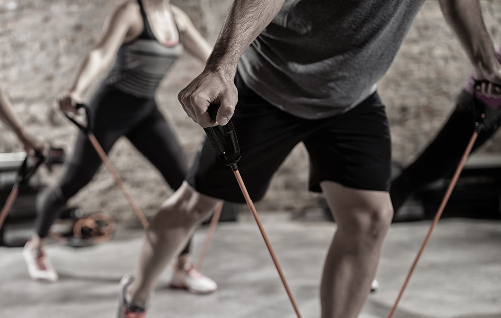 Close up of man doing lunge in the gym using resistance bands