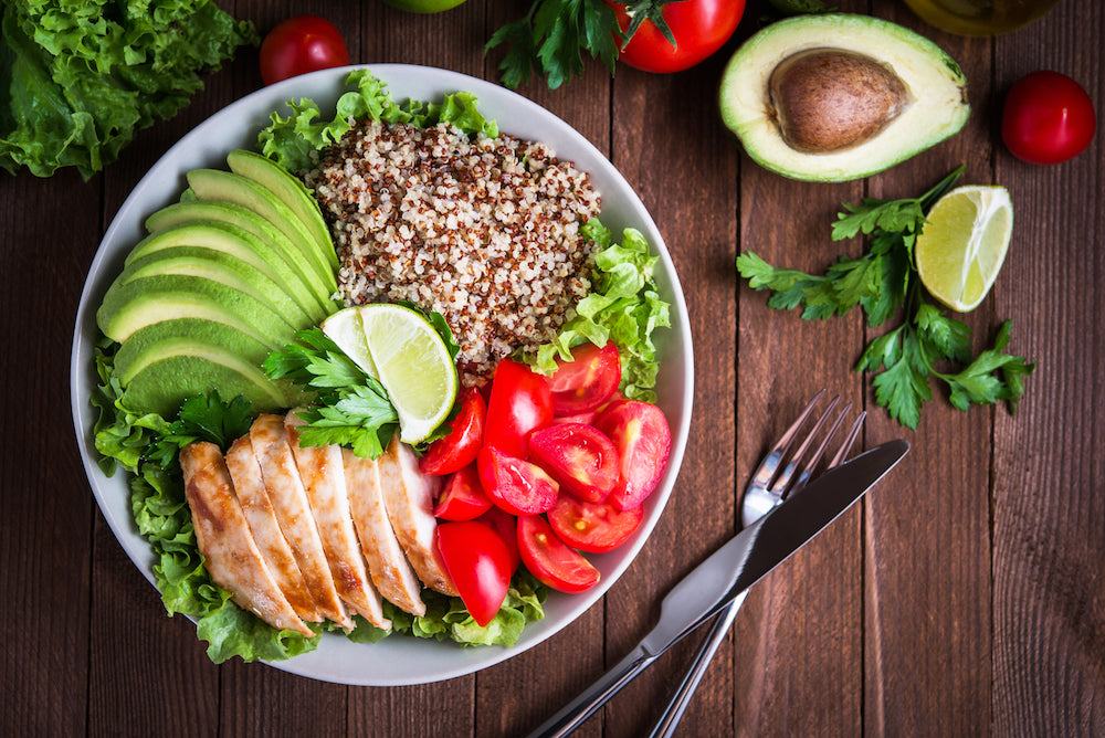 Balanced meal of chicken, avocado, tomato, quinoa on a nice plate setting