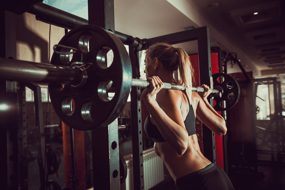 Fit woman doing barbell squat in gym