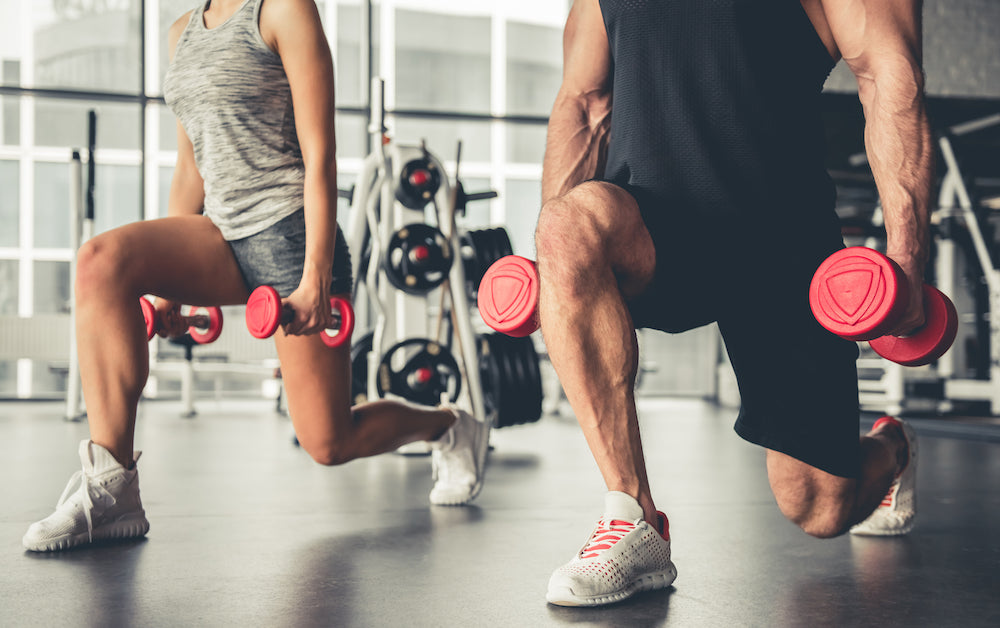 Man and woman performing lunges with free weights in a gym