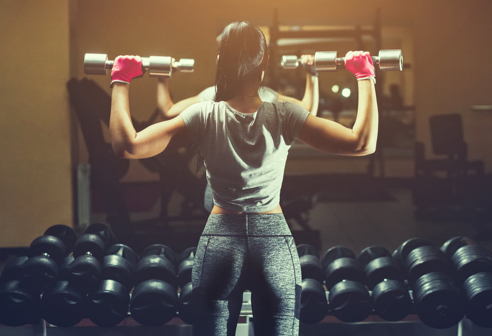 Image of back of woman lifting two barbells