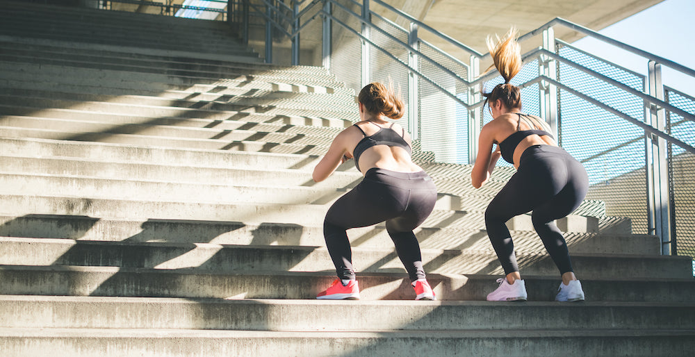 Two women performing squat jumps on stairs
