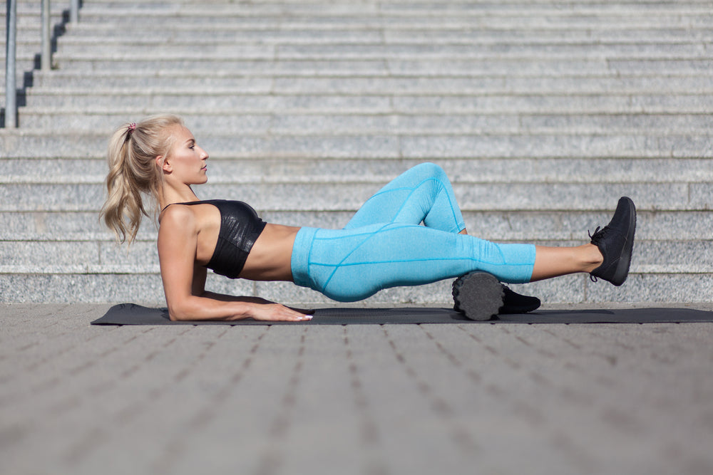Woman using to foam roller to stretch calves