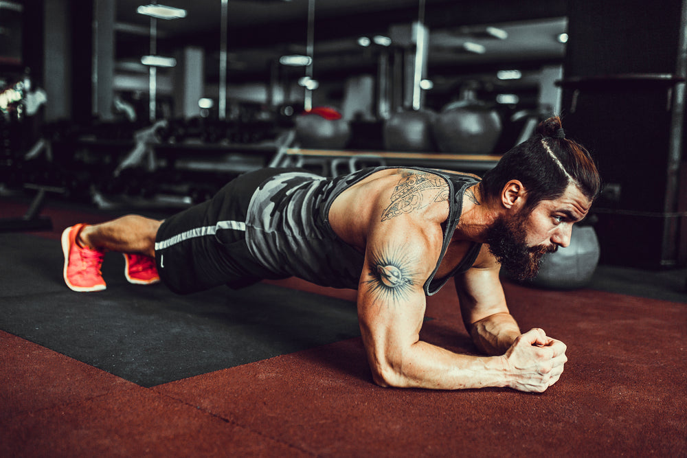 Man preforming jump plank in gym