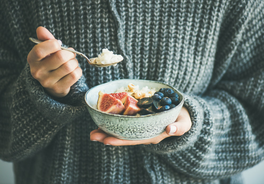 Woman in wintery knitted sweater holding a bowl of porridge with fresh fruit