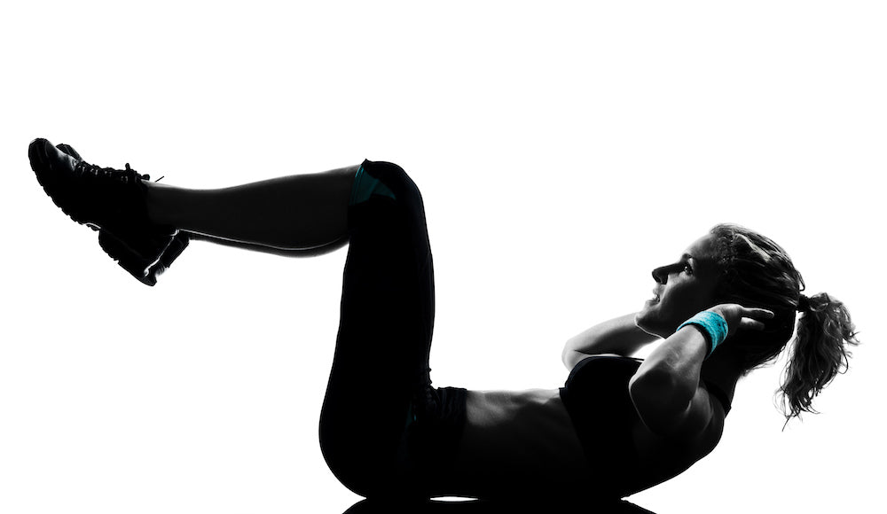 Silhouette of a fit woman doing a crunch exercise