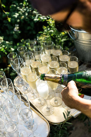 A magnum of Cap Classique being poured into champagne flutes at a Wild Wine Club event at Mawgan Porth Beach