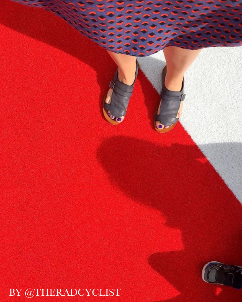 picture of feet with sandals on red floor with shadows being cast