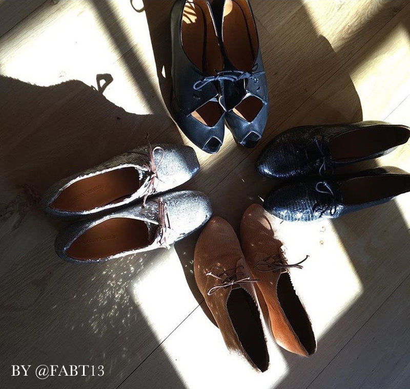 beautiful lit shadowed picture of four shoes facing each other on wooden floor