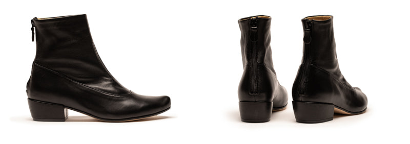 A black women's ankle boot next to a pair of boots on white floor