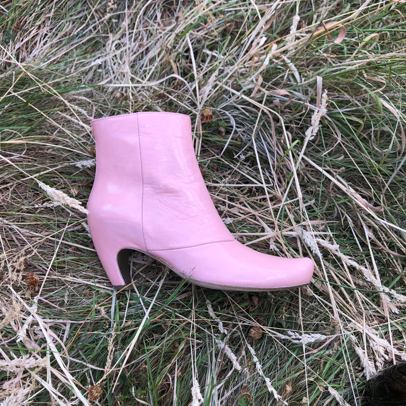 Bubblegum pink mid heel ankle boot by designer Tracey Neuls, displayed on dry grass