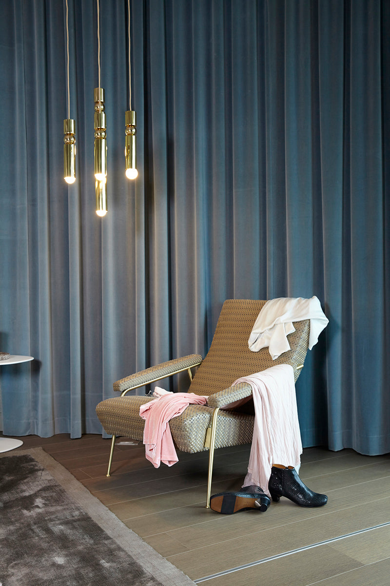 shoes and clothing draping around a chair with a rug and curtains