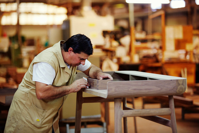 man working in a factory building furniture
