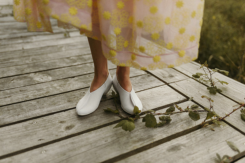 bride with white gene wedding shoes with a yellow and pink wedding dress