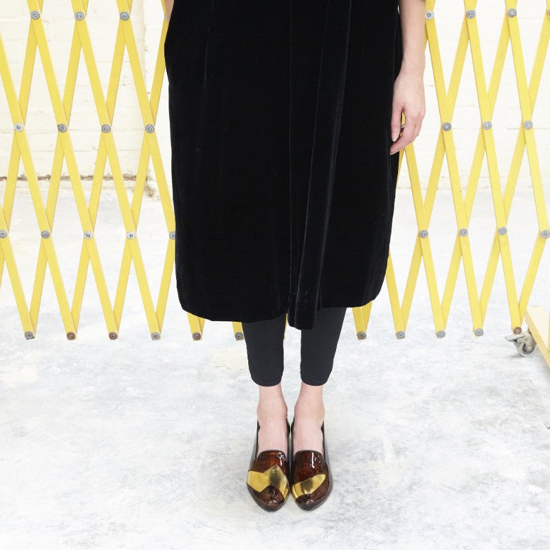 Woman in black stood in front of yellow metal shutter wearing patent brown loafers.