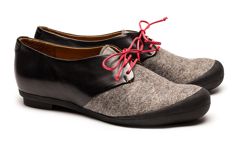 pair of leather and grey felt flat shoes with red laces