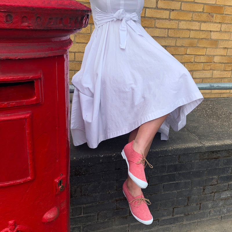 Girl in white dress and red twill Tracey Neuls SS20 sneakers dances next to London postbox