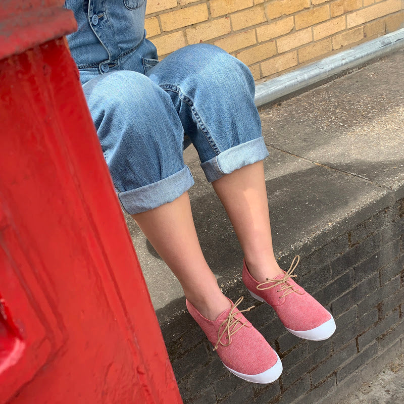 Model in blue jeans and red and white sneakers by Tracey Neuls, sits beside a London postbox