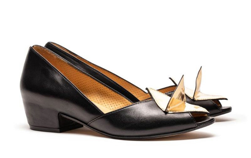 A pair of black italian leather mid heel slip on women's shoes with folded gold leather detail