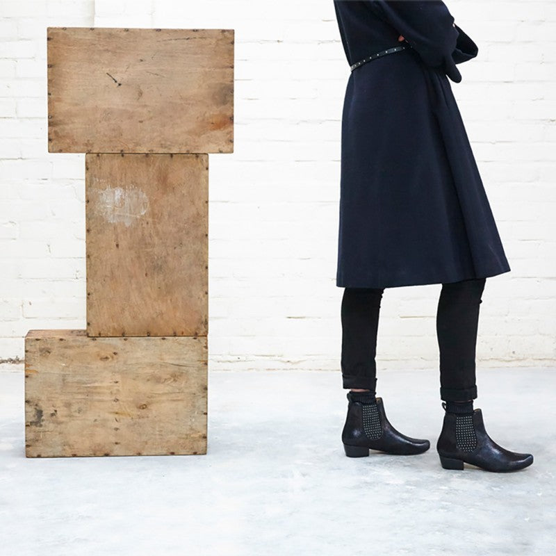 Woman in black wearing heeled chelsea boots with silver studs by designer Tracey Neuls