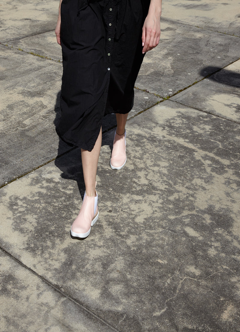 Model wears black maxi dress and pale pink rubber sole chelsea boots by designer Tracey Neuls