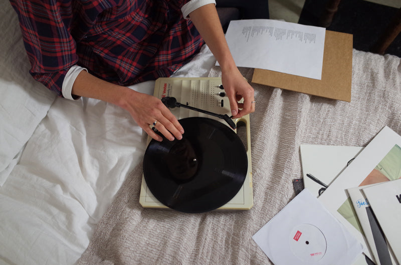Kitty Finer playing a record on the Tracey Neuls bed