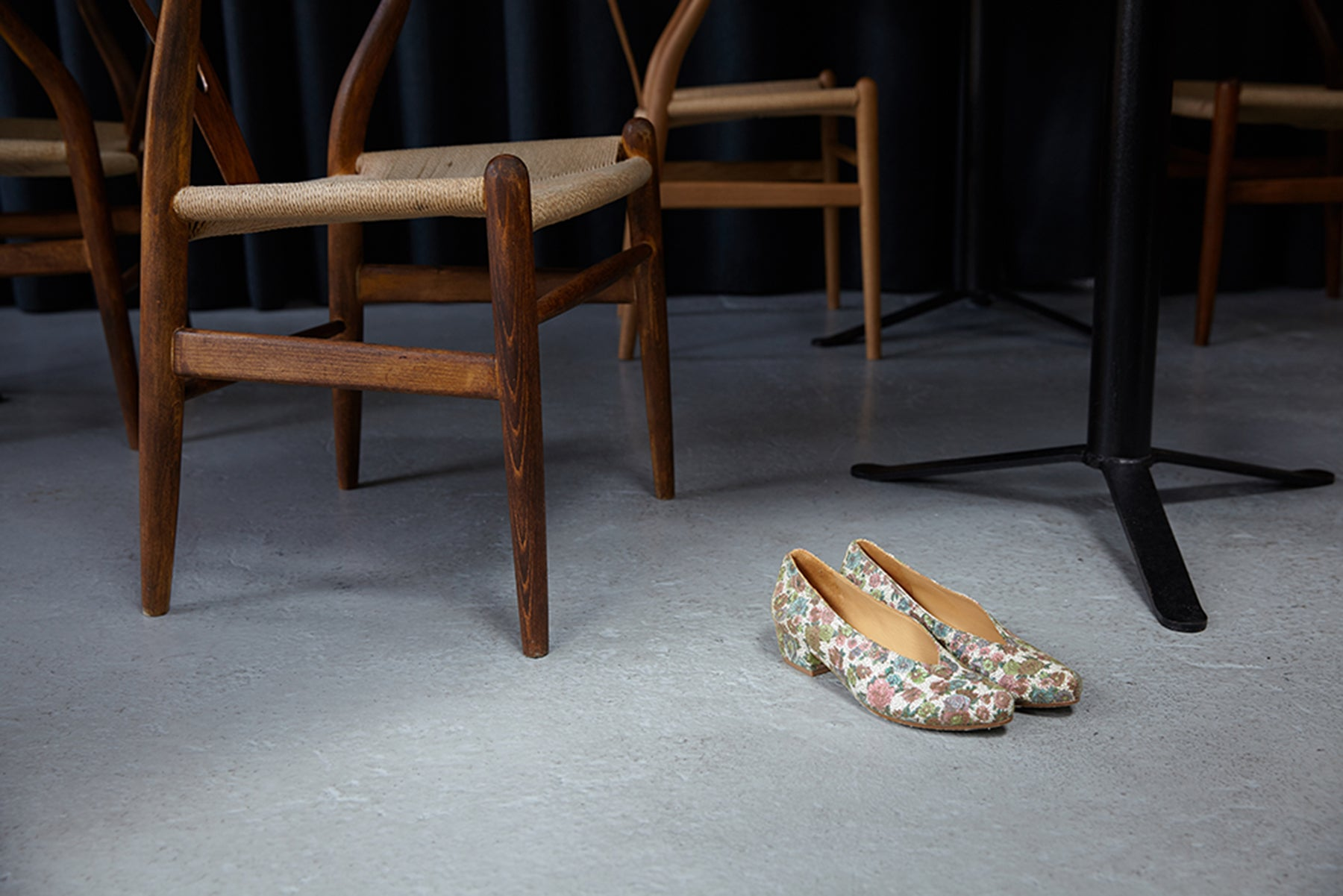 Wooden chairs and a pair of beautiful flower print leather slip-on mid-heels by Tracey Neuls