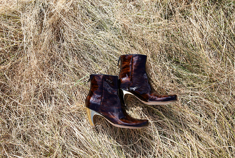 a pair of mahogany brown patent high heel ankle boots lying in the grass