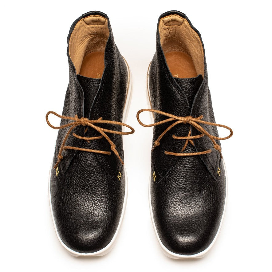 A pair of luxury women's desert boots in black with brown laces, on a white background