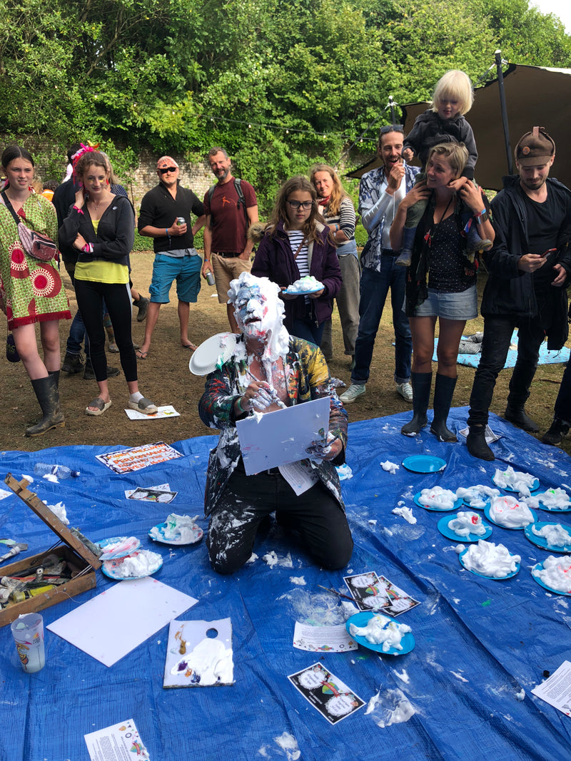 Man dressed as clown covered in paint, on his knees in front of audience at festival