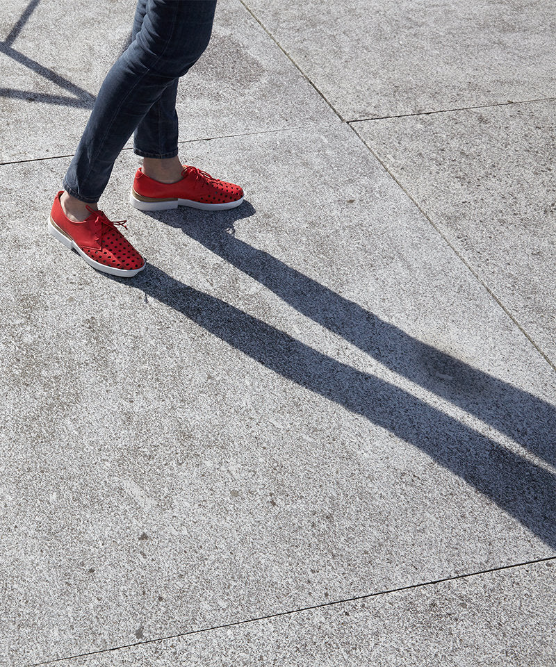 Model with shadow, wearing bright red designer lace ups with white soles by London brand Tracey Neuls