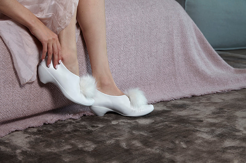 Girl putting on white shoes with a white pom pom, at the edge of a bed