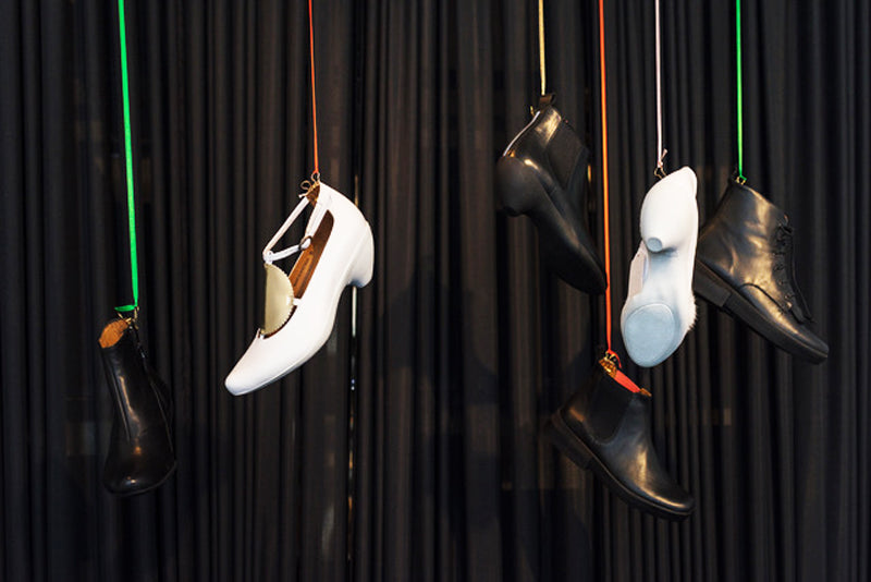 Hanging black and white shoes displayed against a black curtain in shoe shop