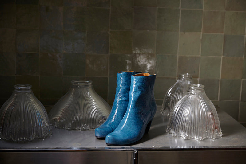 Blue patent leather snug boots on table in front of tiles