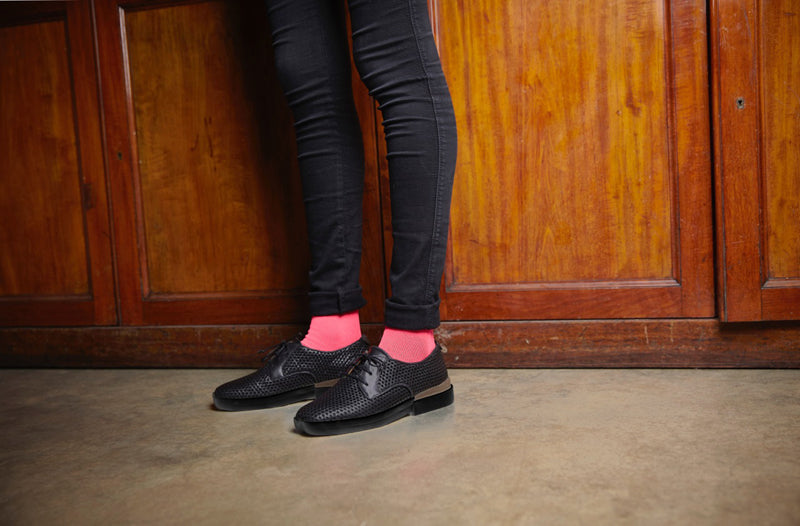 Person wearing pink glittery socks and black shoes