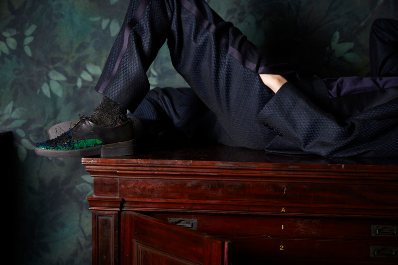 Person lying down on table with glittery socks and wearing a black suit