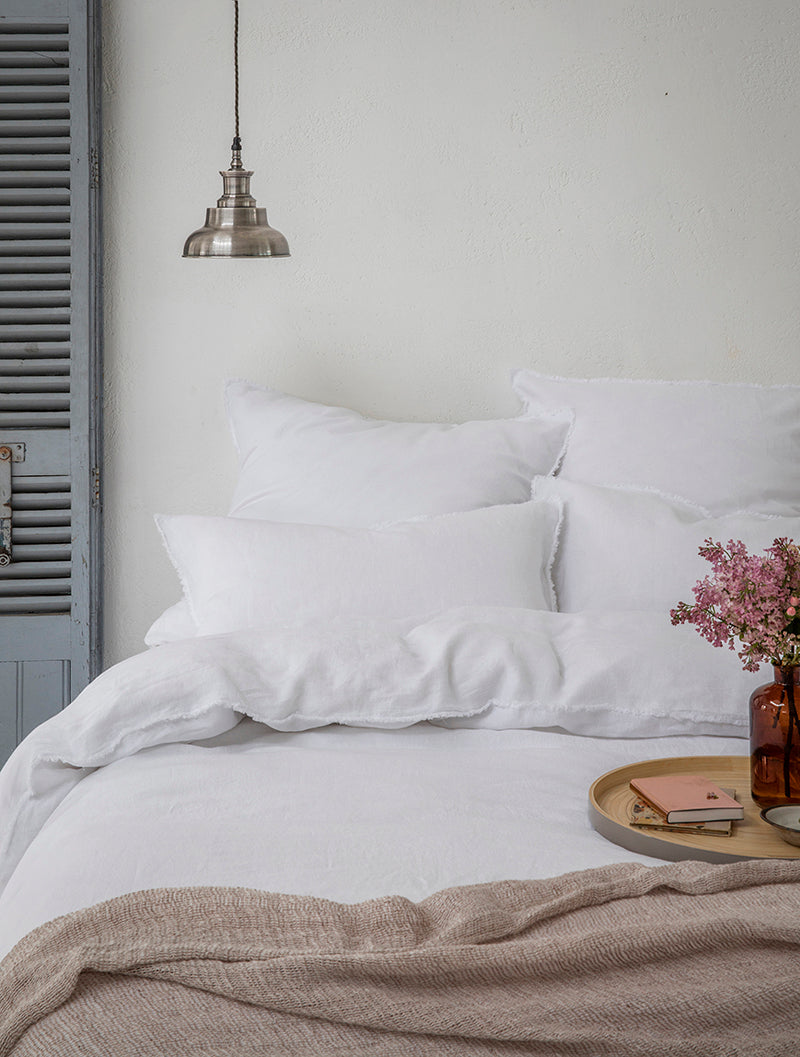 Image of white bed with hanging light and brown blanket