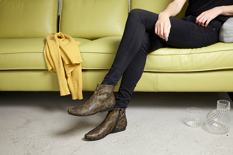 Tracey Neuls gold lala boot shoes with lace in Elementary store Shoreditch Redchurchstreet lime green yellow sofa Elementary store white cushion and pink cushion on grey sofa, minimal stylish scandinavian interior design